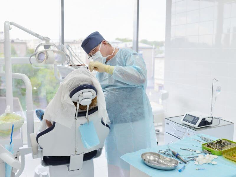 Dental surgeon having wisdom tooth removal operation in clinic.